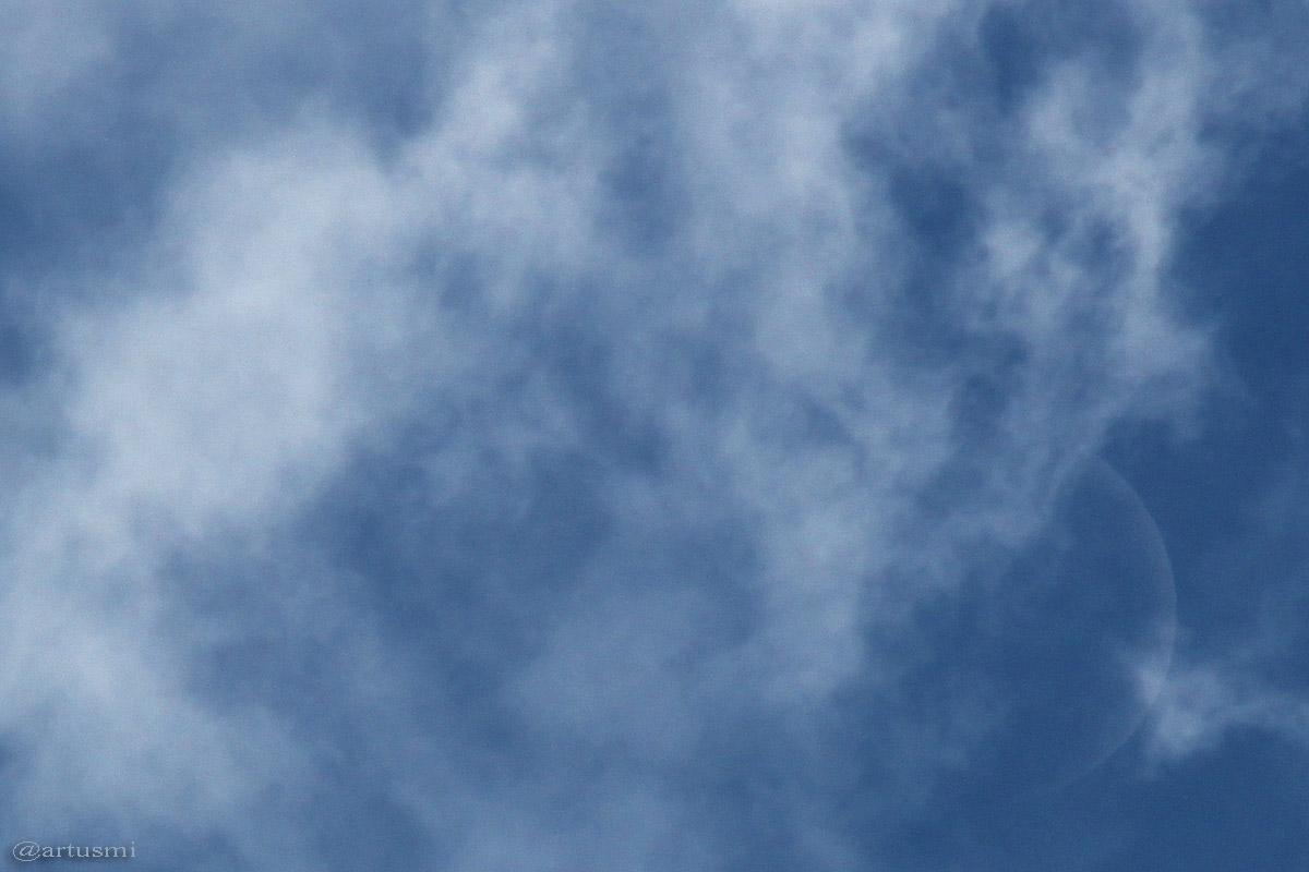 Ausschnittsvergrößerung vom zunehmenden Mond zwischen Wolken am Taghimmel.