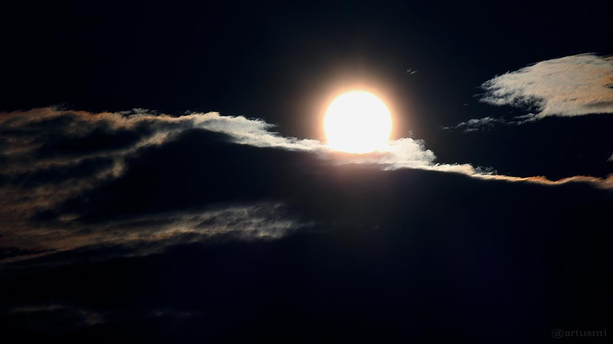 Sonne mit Hof verschwindet hinter irisierenden Wolken