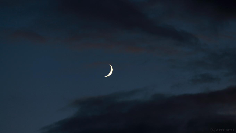 Zunehmende Mondsichel zwischen Wolken