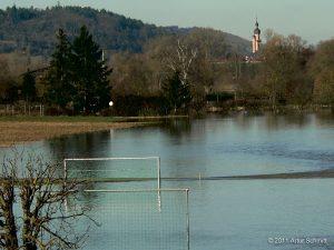 Hochwasser am 16.01.2011. Blick über den überfluteten Fußballplatz auf die Kirche von Eibelstadt.