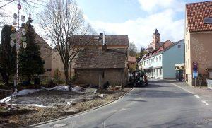 Baustelle in der Hauptstraße am Place de Bernières-sur-Mer - Der gegenüber dem Place de Bernières-sur-Mer liegende kleine Platz mit Backhäusle und Brunnen wird in die Verschönerung mit einbezogen. Er soll zudem mit einer E-Bike-Ladestation versehen werden.