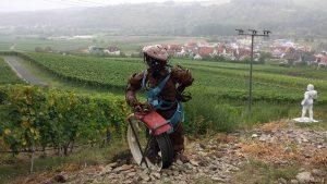 """terroir f Sommerhausen - Skulptur """"zum Wohl"""" von Melina Hillion und Peter Brander - rechts davon die Figur """"Bachus 2014"""" von Bernhard Schwanitz"""